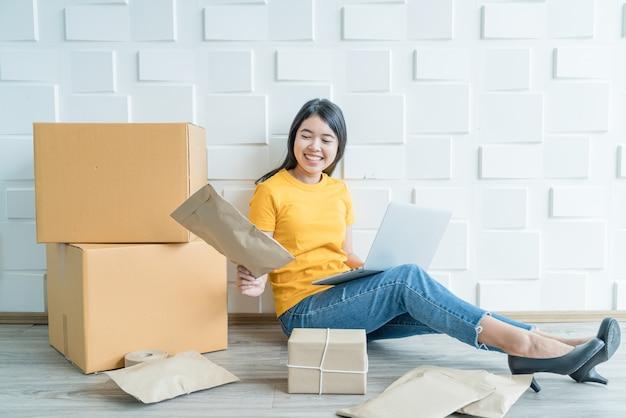 若いアジアのビジネスは、電子メールまたはwebサイトから顧客の注文をチェックし、パッケージを準備するためにコンピューターを使用してオンライン販売者の所有者を立ち上げます Premium写真