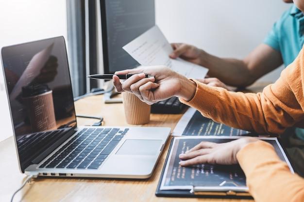 デスクトップコンピューターで開発しているソフトウェアでwebサイトプロジェクトに協力して作業するプログラマー Premium写真