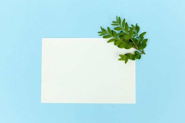 空白の紙カードを使ってデスクトップモックアップ、ぼろぼろの白いテーブル背景に枝空きスペース。スタイルストックフォト、webバナー。フラットレイ Premium写真