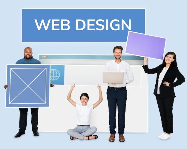 Wedデザインボードを持っている幸せな多様な人々 無料写真