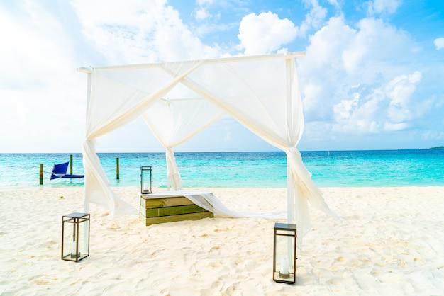 熱帯のモルディブリゾートと海とビーチでの結婚式のアーチ Premium写真