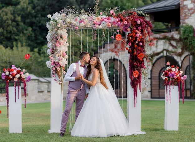 Свадебная арка на заднем дворе и счастливая свадьба пара на открытом воздухе перед свадебной церемонией Бесплатные Фотографии