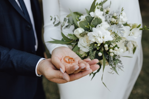 Wedding bands in the hands of bride and groom and with beautiful wedding bouquet made of greenery and white flowers Free Photo
