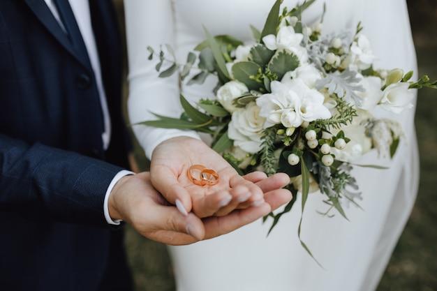 신부와 신랑의 손에 녹지와 흰색 꽃으로 만든 아름다운 웨딩 부케와 웨딩 밴드 무료 사진