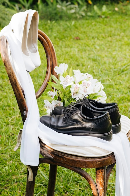 Wedding black shoes and white high heels with flower bouquet on wooden chair in the garden Free Photo