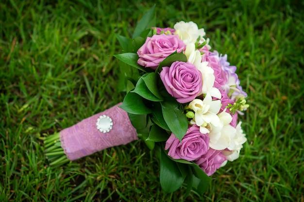 Wedding bouquet of flowers lying on green grass Premium Photo