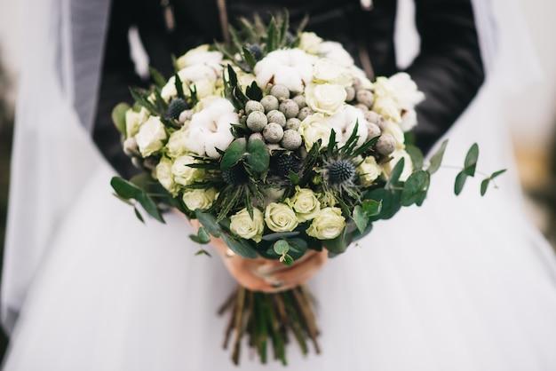 花嫁の手の中のウェディングブーケ。白いバラ、綿、いばら、緑のヒムキブーケ Premium写真