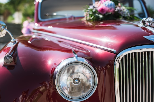 Wedding bouquet on red vintage wedding car. Premium Photo