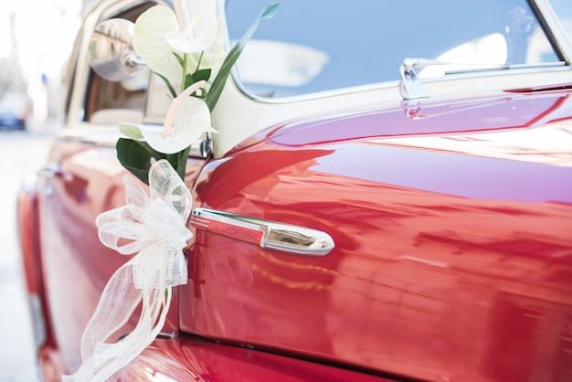 Wedding bouquet on red vintage wedding car. Premium Photo