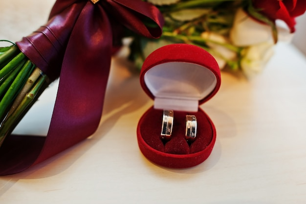 Wedding bouquet of red and white rose and ribbon with wedding rings on box Premium Photo