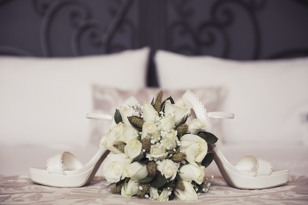 Wedding bouquet and shoes on bedroom Premium Photo