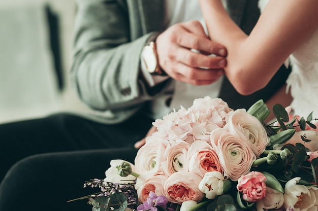 Wedding bouquet with blurred bride and groom Premium Photo