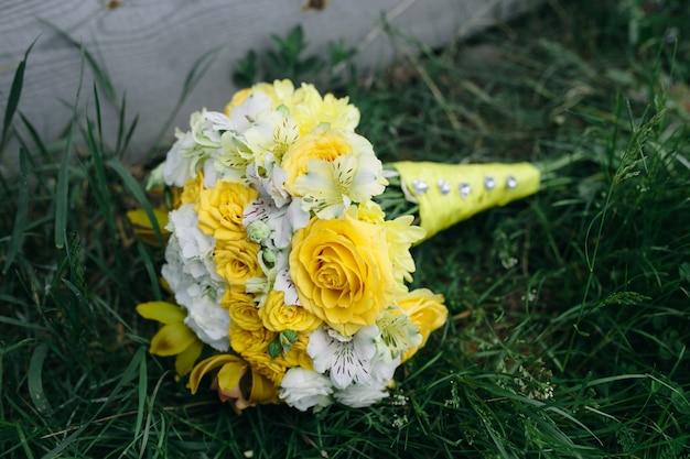 草の上に横たわっている黄色いバラのウェディングブーケ 無料写真