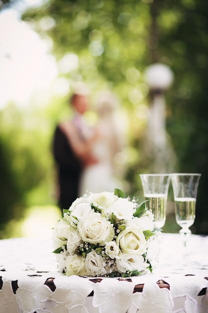 Свадебный букет невесты с белыми розами на столе в саду Premium Фотографии