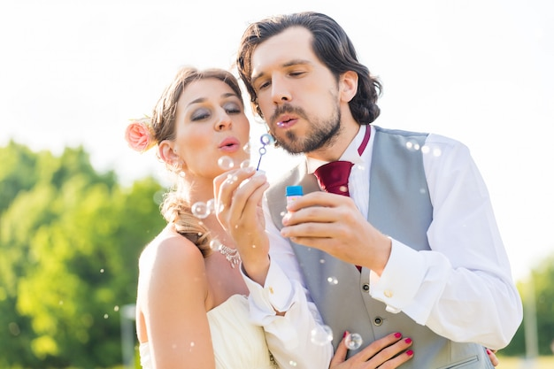 Wedding bride and groom blowing bubbles outside on field Premium Photo