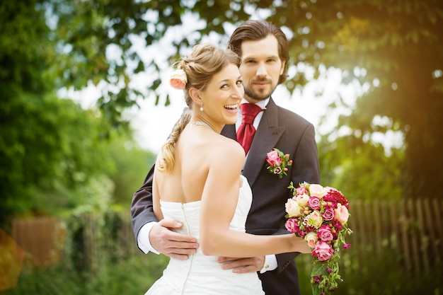 Wedding bride and groom in a meadow, with bridal bouquet Premium Photo