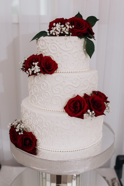 Wedding cake decorated with red roses Free Photo