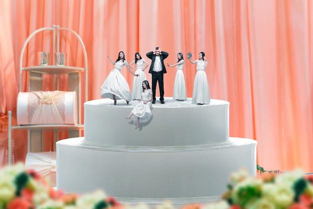 Свадебный торт, фигурки жениха и невесты Premium Фотографии
