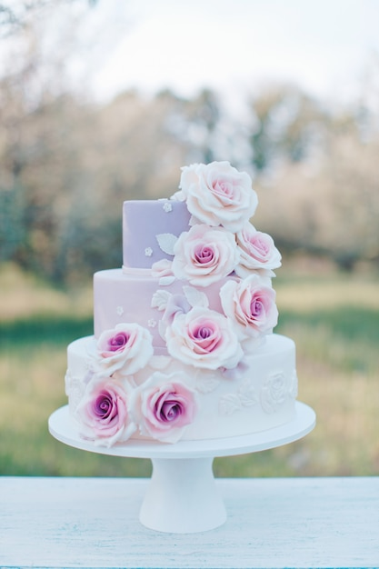 Wedding cake in pastel colors decorated with realistic pink roses on a blurred background of the garden, selective focus Premium Photo