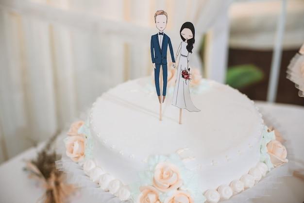 Wedding cake with funny figurines of groom and bride. Premium Photo