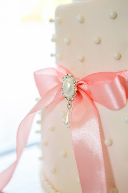 Wedding cake with white icing and pink bow Premium Photo