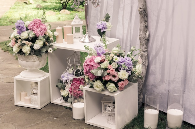 Wedding ceremony decorations bouquets of flowers/ candles in restaurant outdoors. Premium Photo
