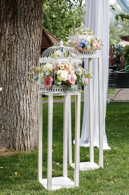 Wedding ceremony decorations bouquets of roses and eustoma in restaurant outdoors. Premium Photo
