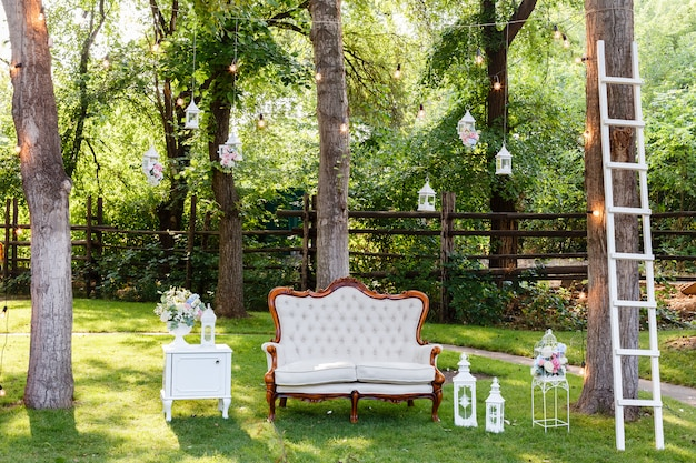 Wedding ceremony decorations bouquets of roses, sofa, staircase in restaurant outdoors. Premium Photo