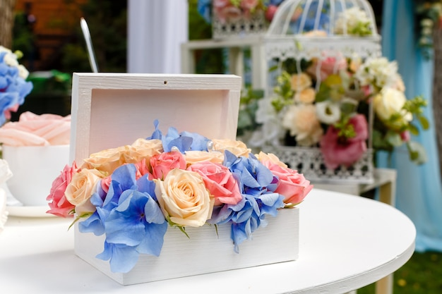 Wedding ceremony decorations bouquets of roses at the table in restaurant outdoors. Premium Photo