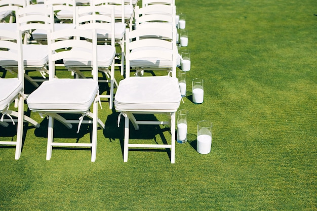 Wedding ceremony in nature. rows of white chairs on the lawn. Premium Photo