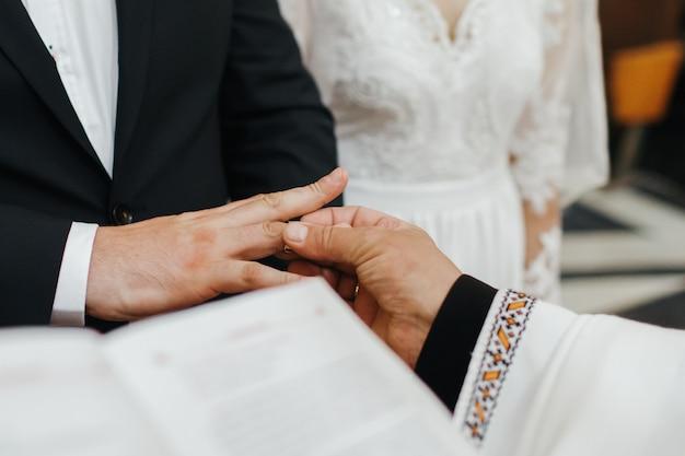 Wedding ceremony. priest puts wedding ring on groom's hand Free Photo