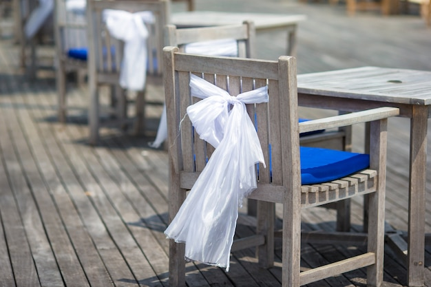 Wedding chairs decorated with white bows at outdoor cafe Premium Photo