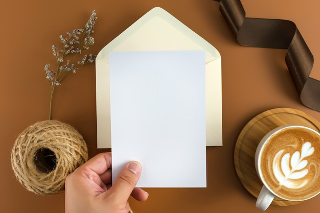 A wedding concept. wedding invitation on brown background with ribbon. Premium Photo