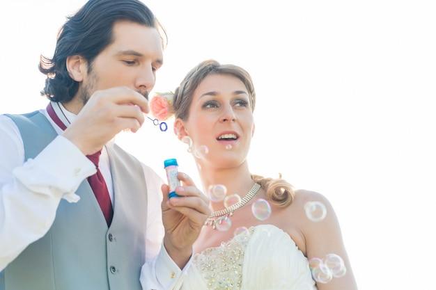 Wedding couple blowing soap bubbles outside Premium Photo