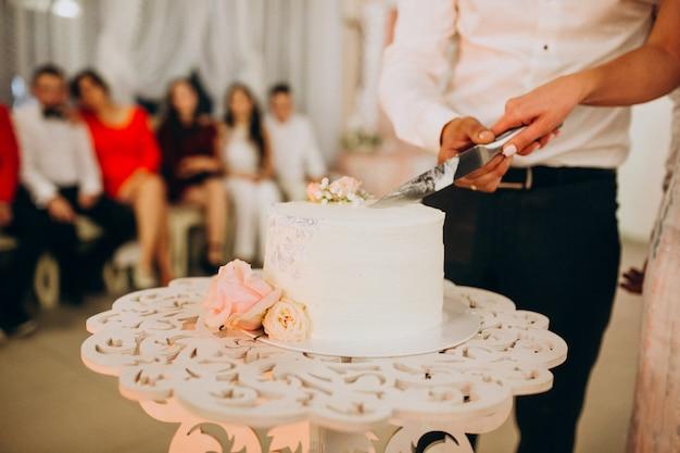 Wedding couple cutting their wedding cake Free Photo