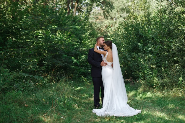 Wedding couple enjoying romantic moments outside.wedding day in the summer. happy emotional bride and groom walking in a green parkin sunny day. groom kissing bride. groom embraces bride in the garden Premium Photo