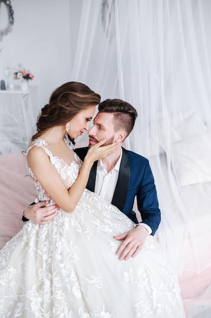 屋内でお互いを抱いて結婚式のカップル。白いドレスの美しいモデルの女性。スーツを着た男。新郎と美の花嫁。 Premium写真