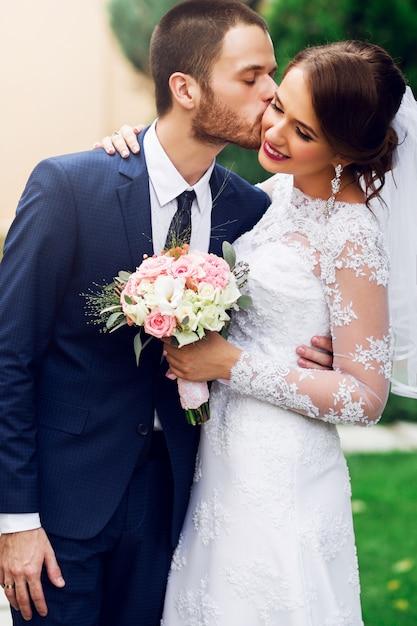 Свадебная пара в любви, целоваться и улыбаться. молодая довольно элегантная невеста и ее красивый жених, позирует в зеленом парке. Бесплатные Фотографии