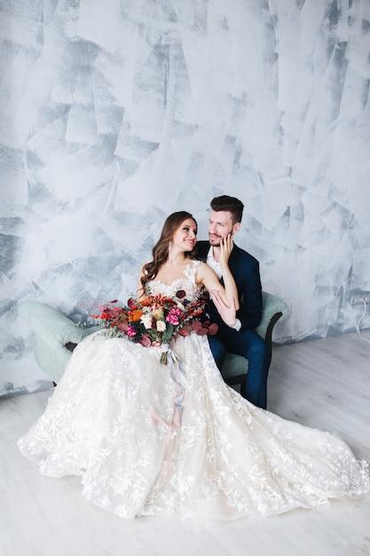 屋内での結婚式のカップルはお互いに抱き合っています。白いドレスの美しいモデルの女性。スーツを着た男。新郎と美の花嫁 Premium写真
