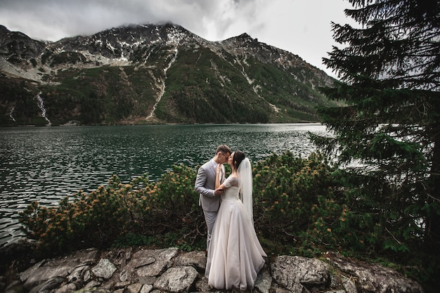 Wedding couple kissing near the lake in tatra mountains in poland, morskie oko Premium Photo