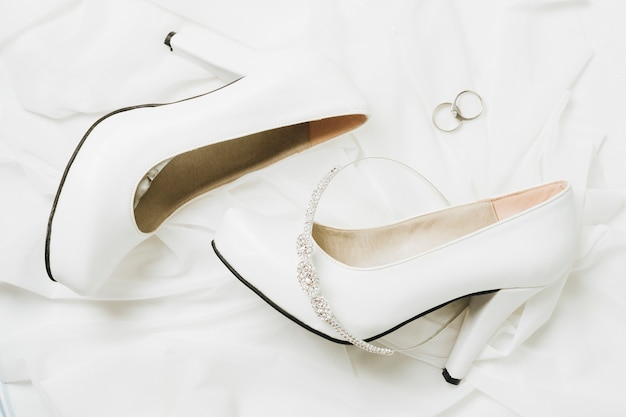 Wedding crown and rings with wedding high heels on white scarf Free Photo