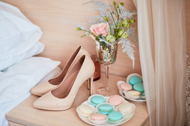 Wedding decor. beige bride's shoes, bouquet and plate with macaroons stand on the table Free Photo
