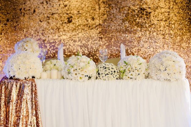 Wedding decor, bouquets of white flowers on the wedding table in restaurant Premium Photo