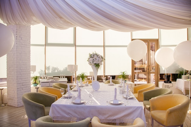 Wedding decor, wedding tables in restaurant with white flowers and huge white balloons Premium Photo