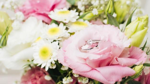 Wedding diamond rings on flower bouquet Free Photo