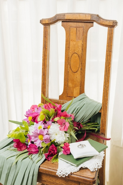 Wedding dress; bible; flower bouquet and wedding rings on wooden chair near the curtain Free Photo
