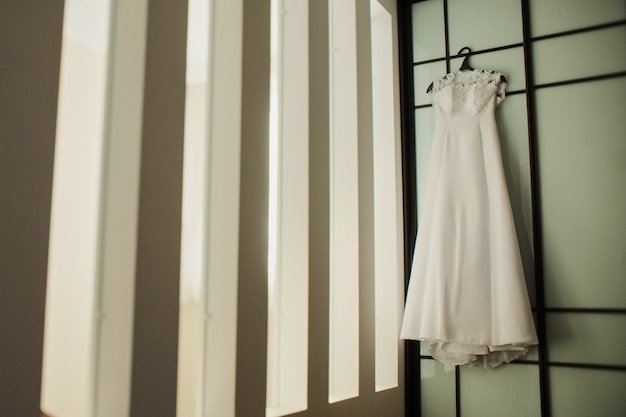 Wedding dress on a hanger near the wall Premium Photo