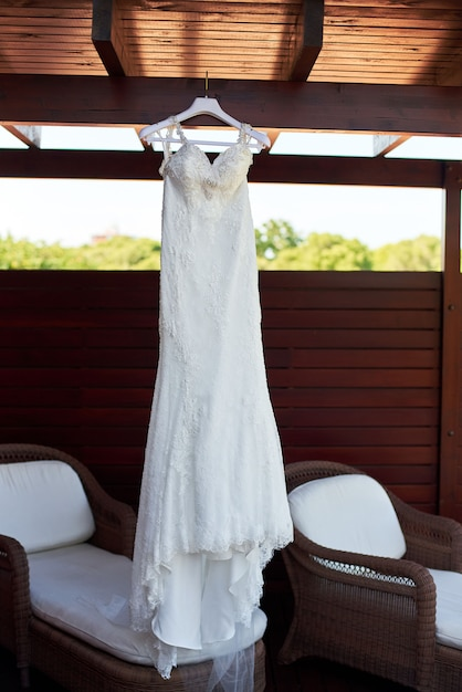 Wedding dress hanging on the ceiling on the balcony Premium Photo
