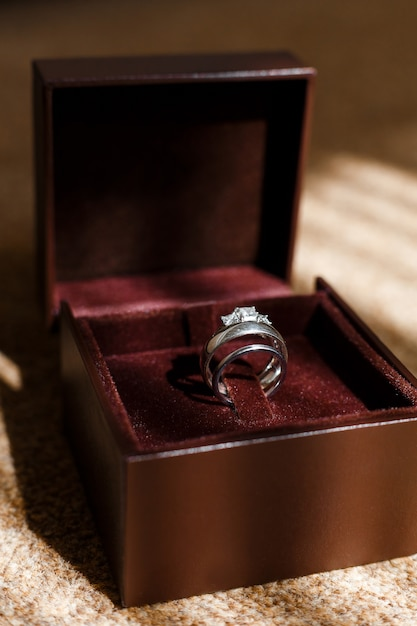 Wedding and engagement rings shining in brown box Premium Photo