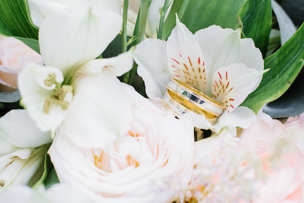 Wedding engagement rings of yellow and white gold are on the wedding bouquet Premium Photo